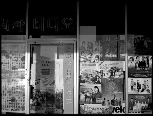 asian video store, video posters, b&w photograph