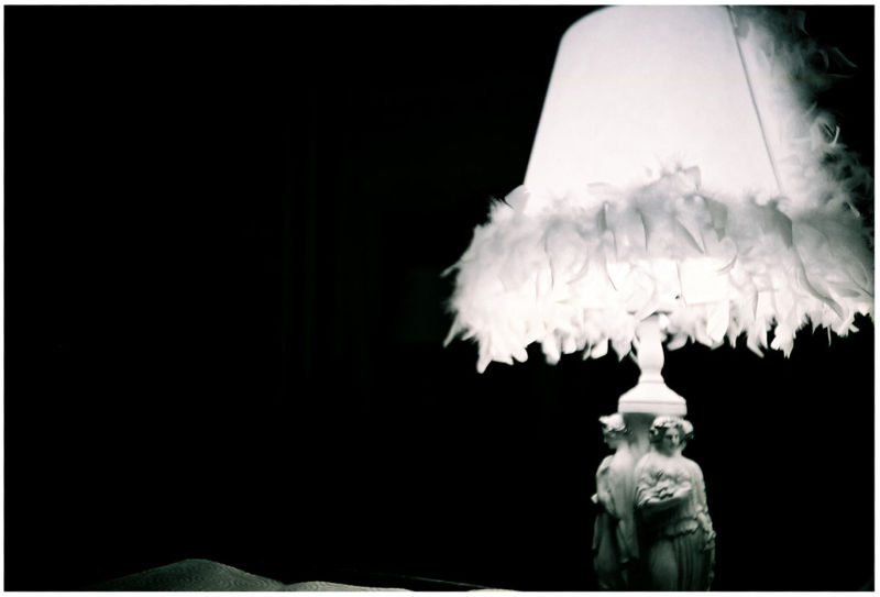 figures on a lamp, lamp in a dark room, photo