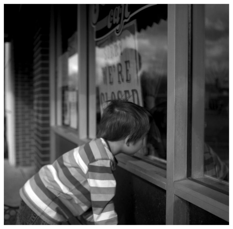 boy looking in a window - grant edwards photograph