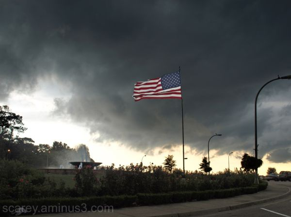 American flag against stormy sky backdrop