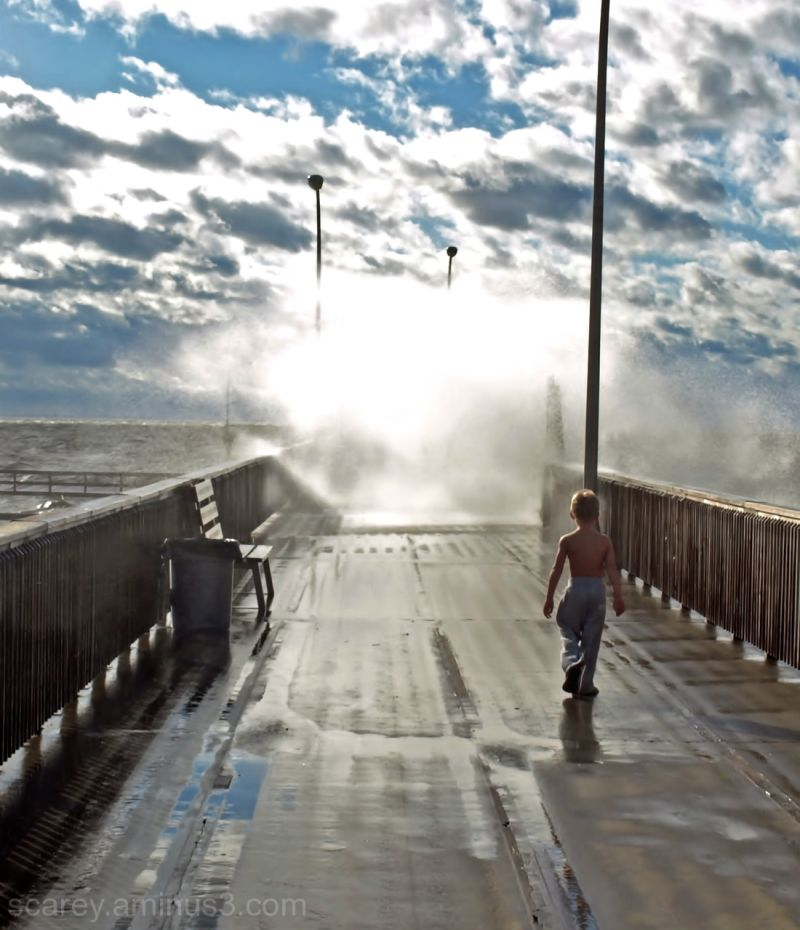 Boy walking on pier during as wave overtops pier