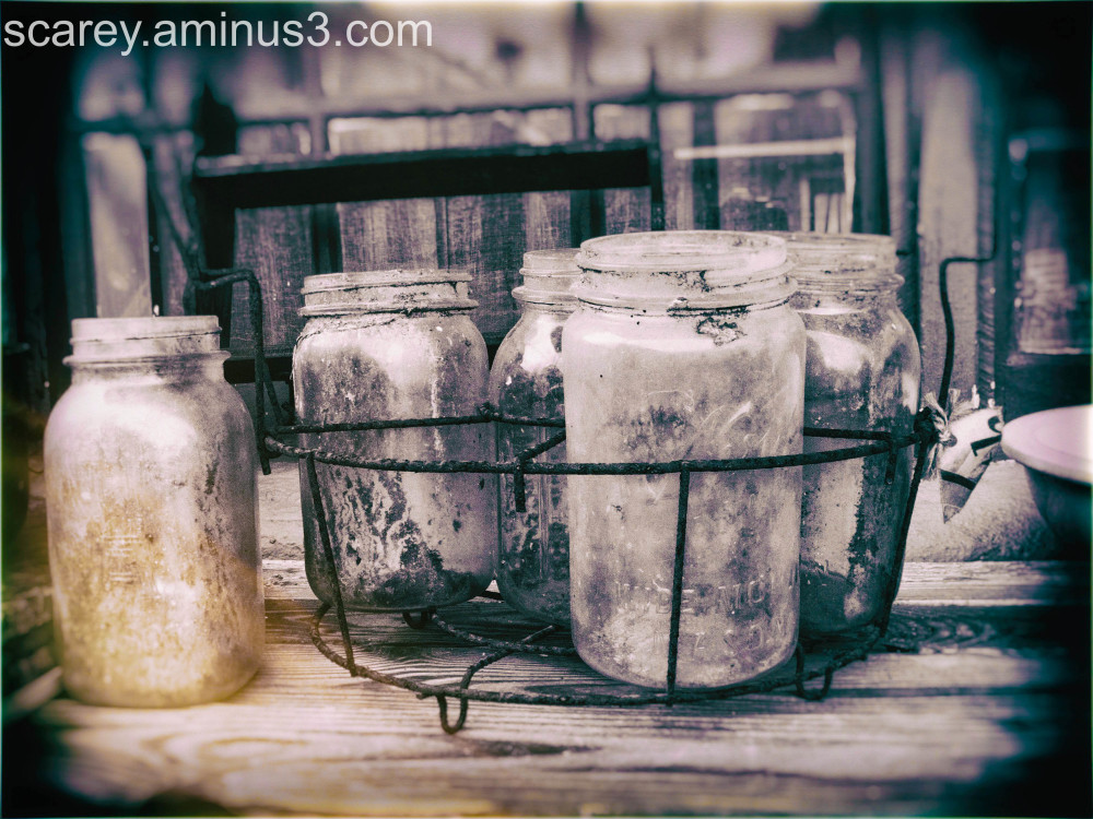 Fruit jars in a rusted wire basket