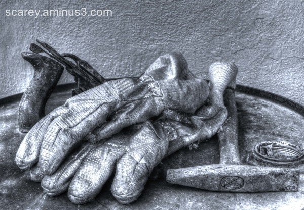 B & W image of workman's gloves and tools