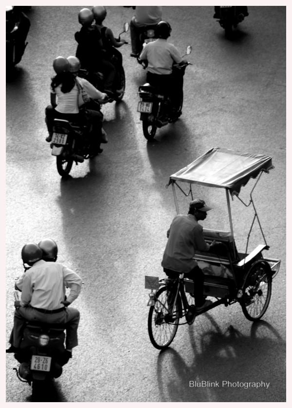Cyclo man working amongst motorbike traffic