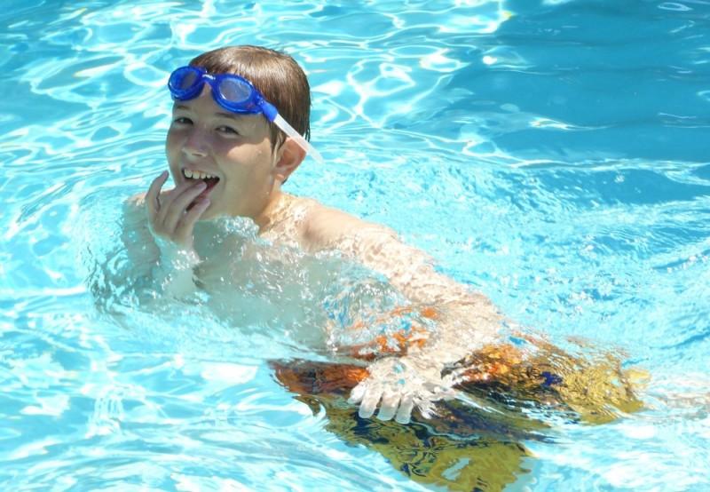 boy in goggles with summer fun in backyard pool