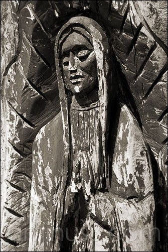 a weathered carving of the Virgin of Guadalupe,