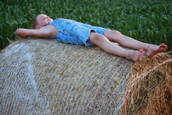 boy resting roundbale