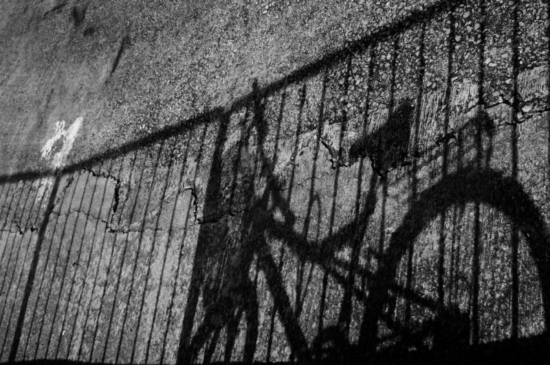 Shadow of a bicycle on a fence
