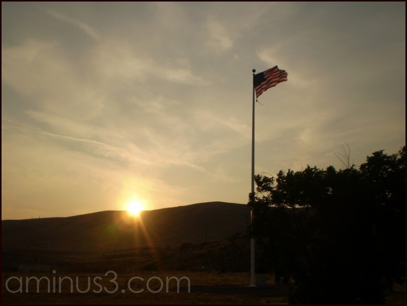 A sunset shining on the American Flag