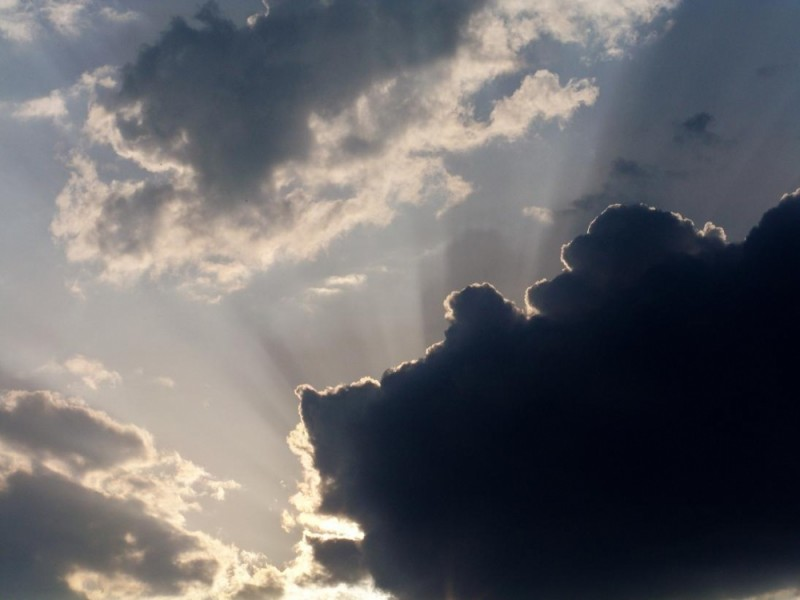 sun hiding behind a dark cloud