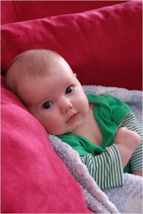 Baby in green on red couch