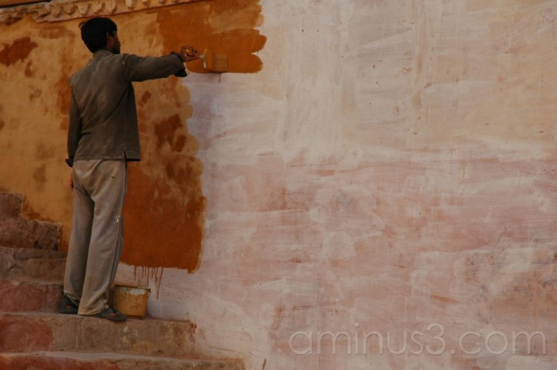 Indian painter touching up Amber Fort in Jaipur