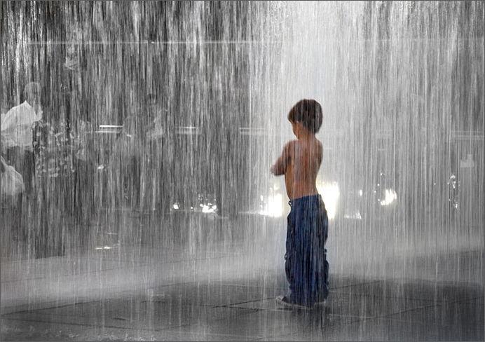 Boy in water fountain