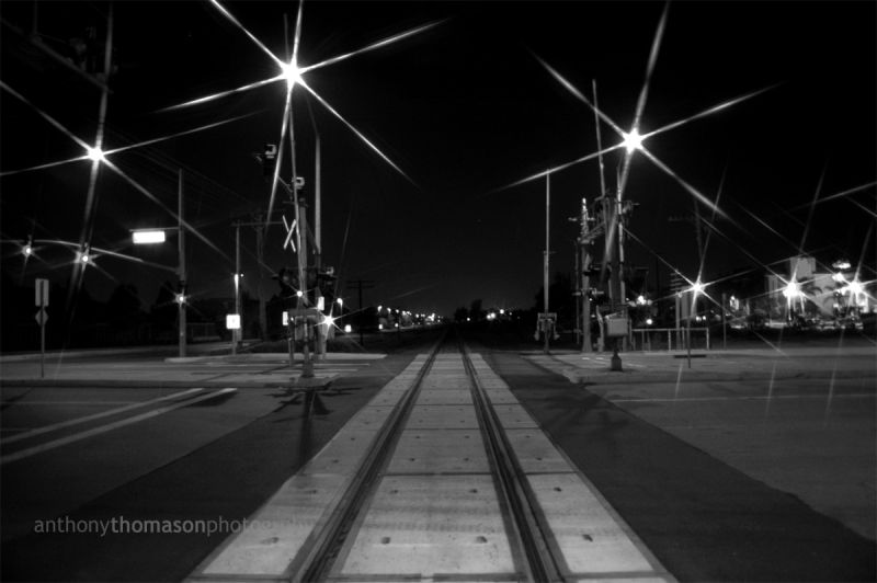 Train tracks in the middle of a city, at night.