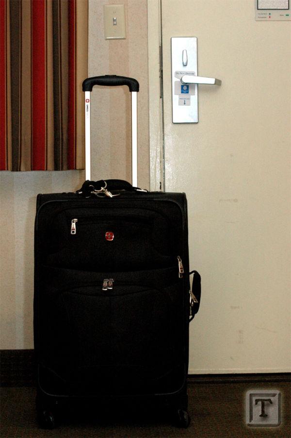 Suitcase by hotel room door