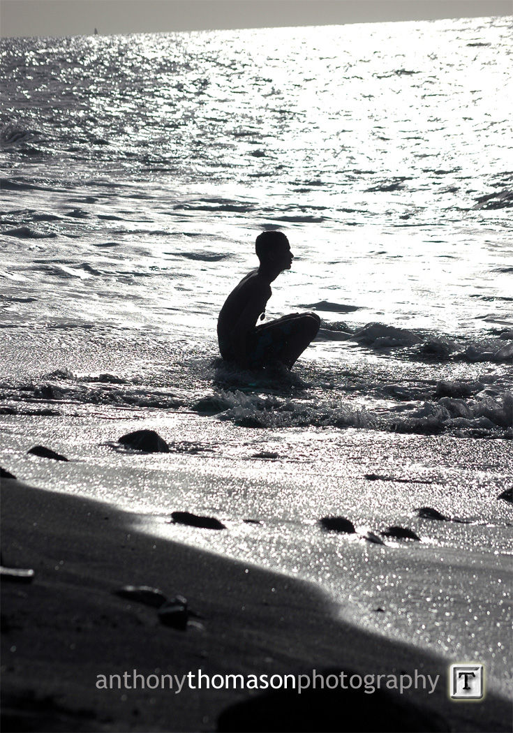 Young man sittin on the shore pondering