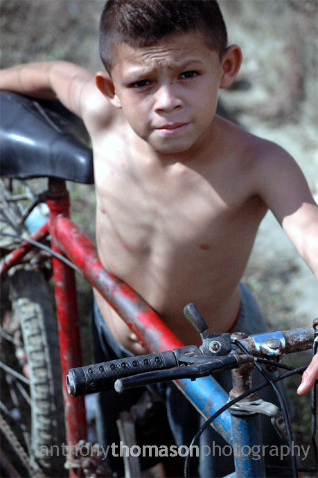 Young boy with bicycle on Honduras Street.