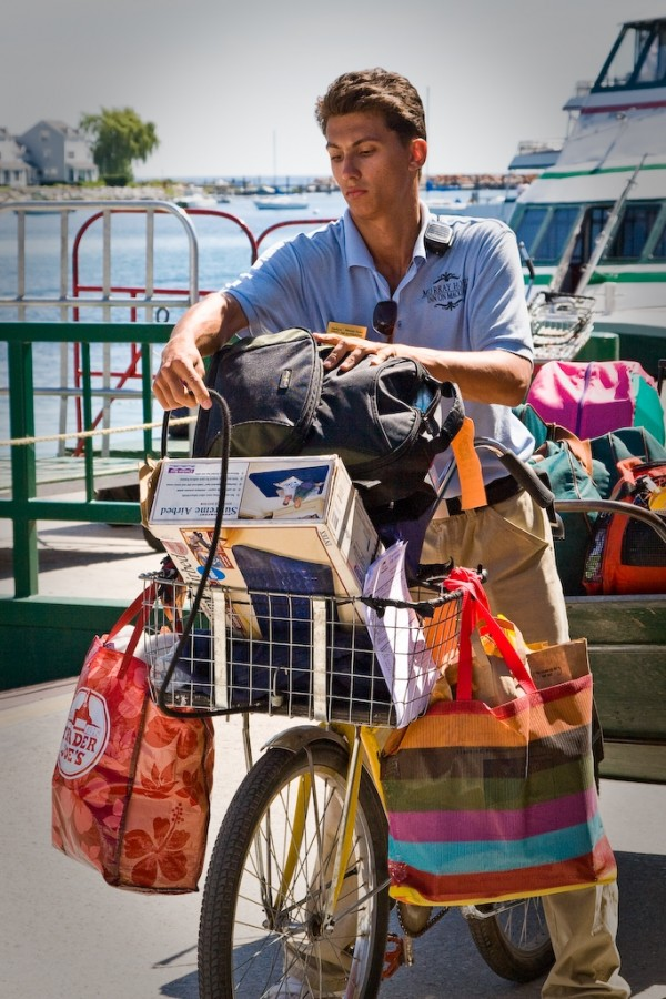 A porter loads luggage on his bicycle