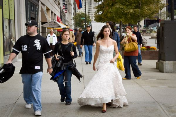 A photographer and bride walk the street