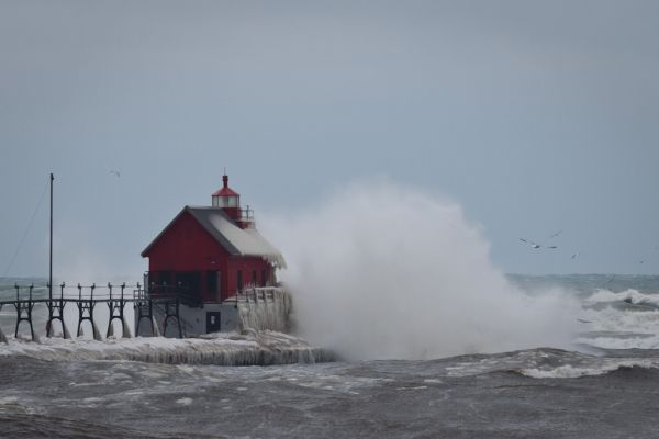 A wave breaks over the Grand Haven Lighthouse