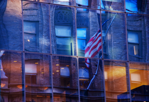 Reflections of a building and US flag