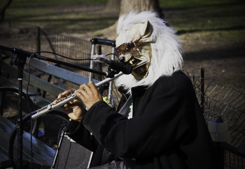 Playing a flute in wolf mask