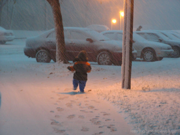 Child walking in snow at night