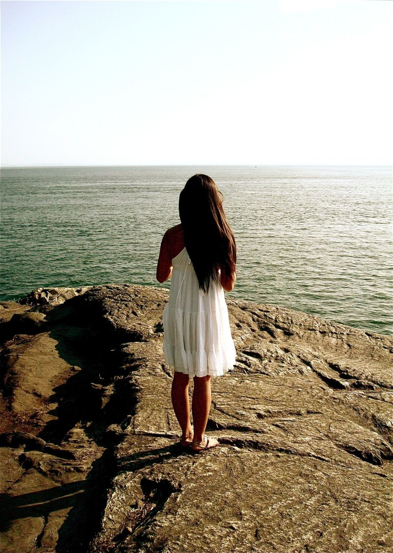 a person in a white dress by the ocean