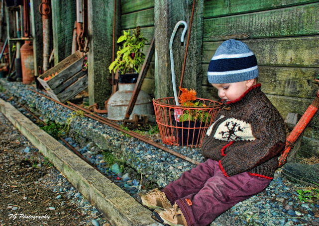 My son sitting outside an old barn around hallowee