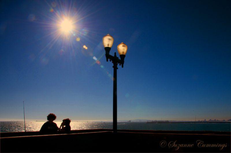 pier lamppost sun sunflare ocean fishing children