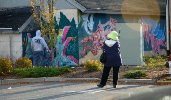 Graffiti artist at work and interested observer