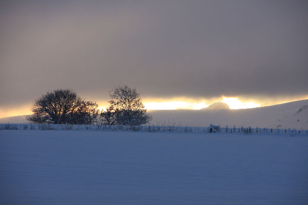 Sun fighting the snow clouds