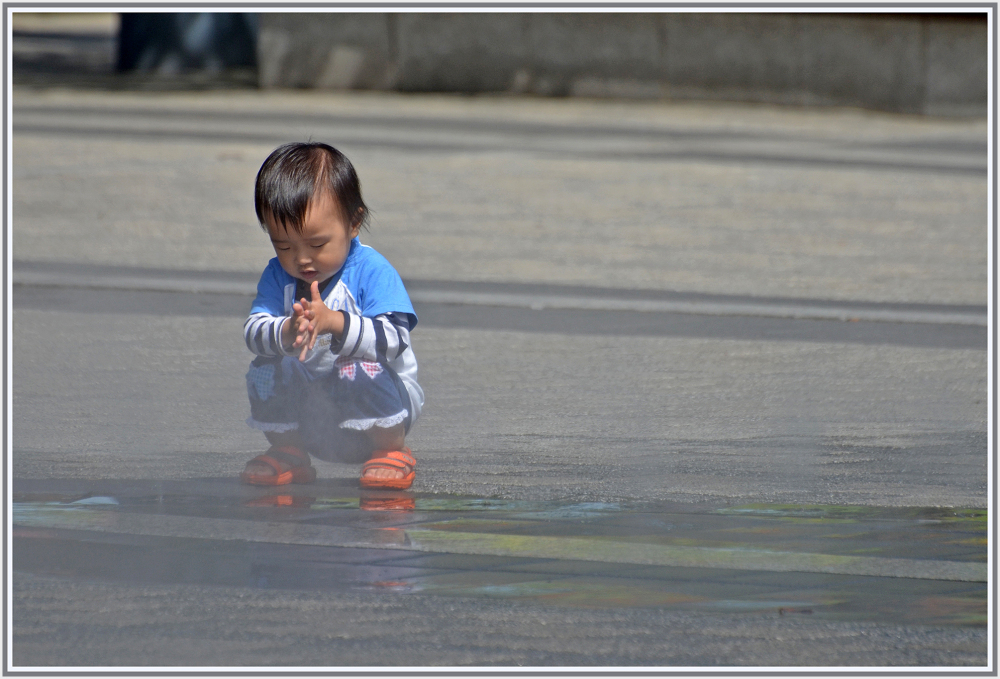 Little boy in a misty fountain in Seoul