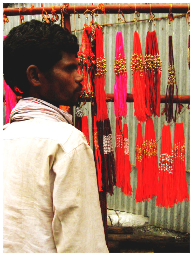 a man selling colourful threads on laxmi road