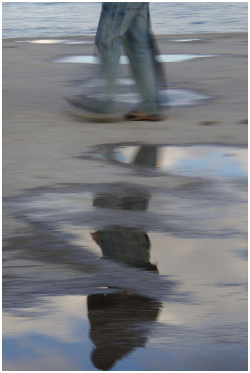 una figura humana andando entre charcos