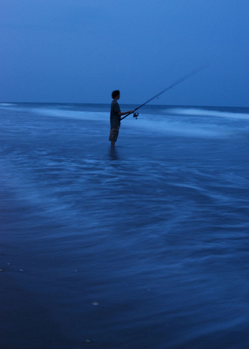 Teenager night fishing in the surf of Topsail