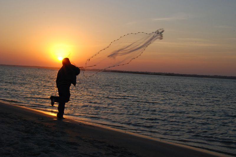 A man throws his net into the water at sunset