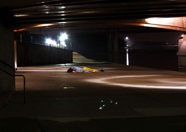 homeless person sleeping under bridge downtown