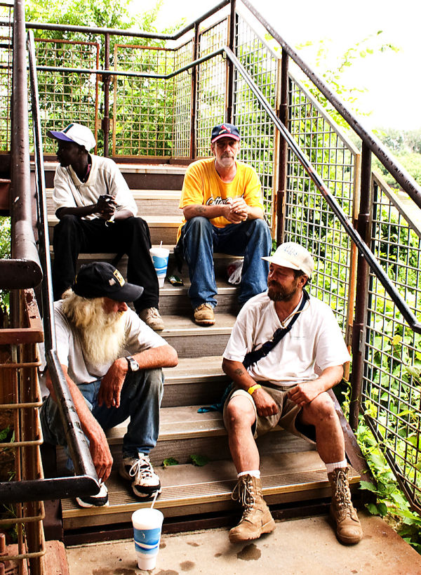homeless men sitting on a stairway