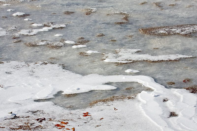 drifting snow and sand on icy river edge