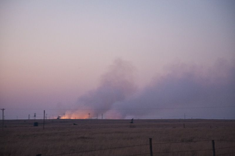 sun sets over burning flint hills prairie