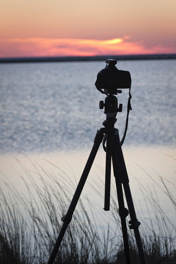 camera on tripod  silhouetted by the sunset