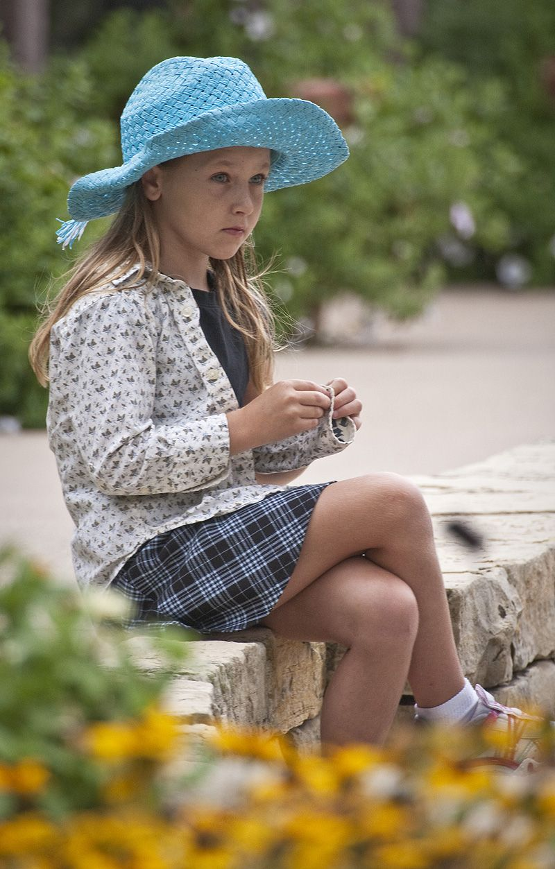 young girl in blue straw hat and plaid skirt