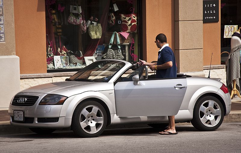 man entering his audi convertable on the plaza