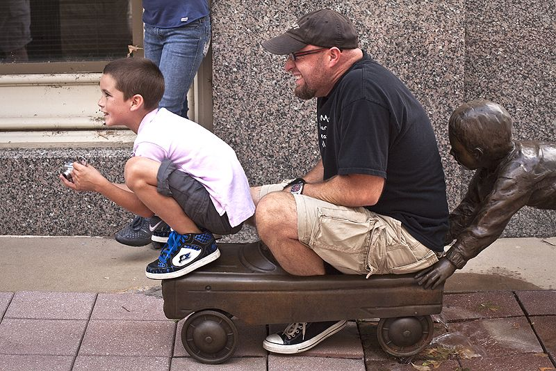 playing on street sculpture in downtown wichita