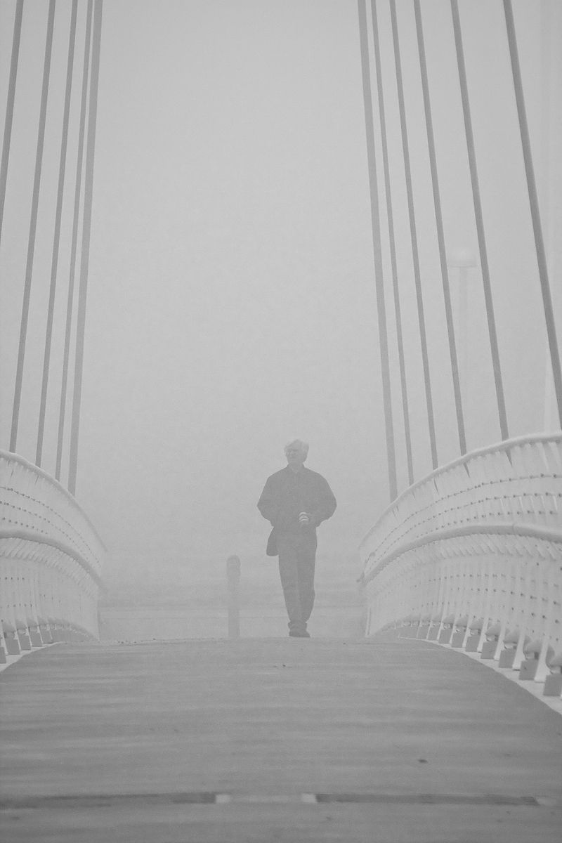 man on foot bridge in morning fog
