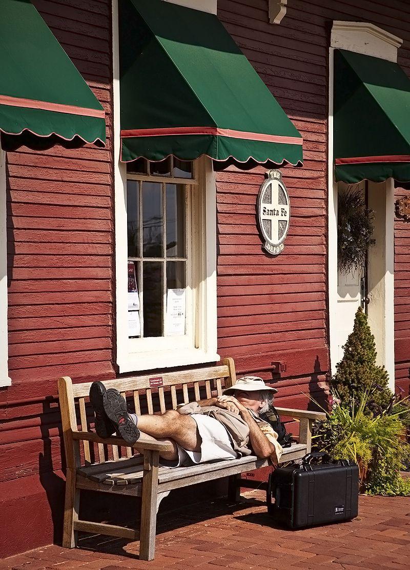 man naps on bench outside railroad station