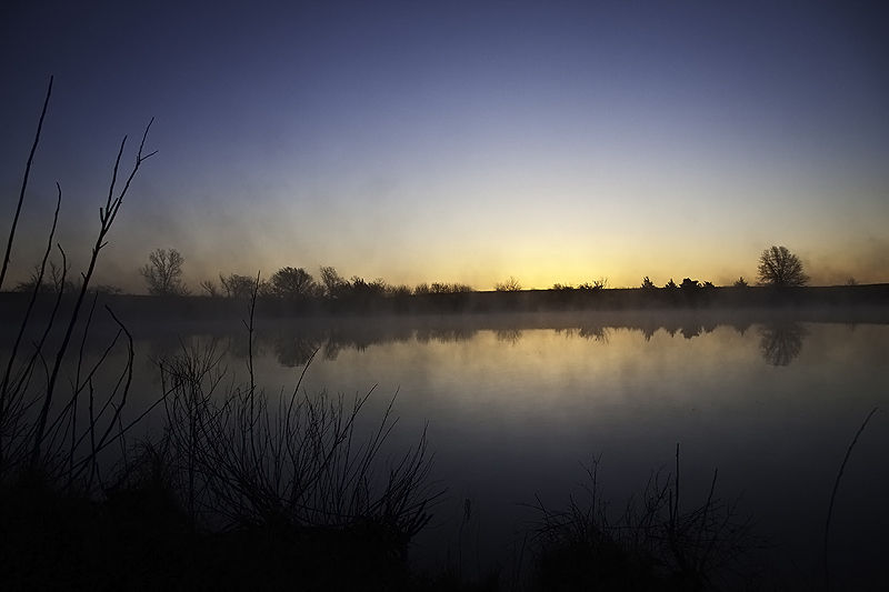 sunrise augmented by mist on pond