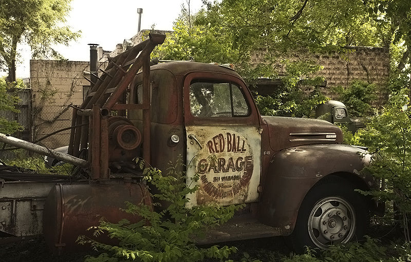 old tow truck in the weeds