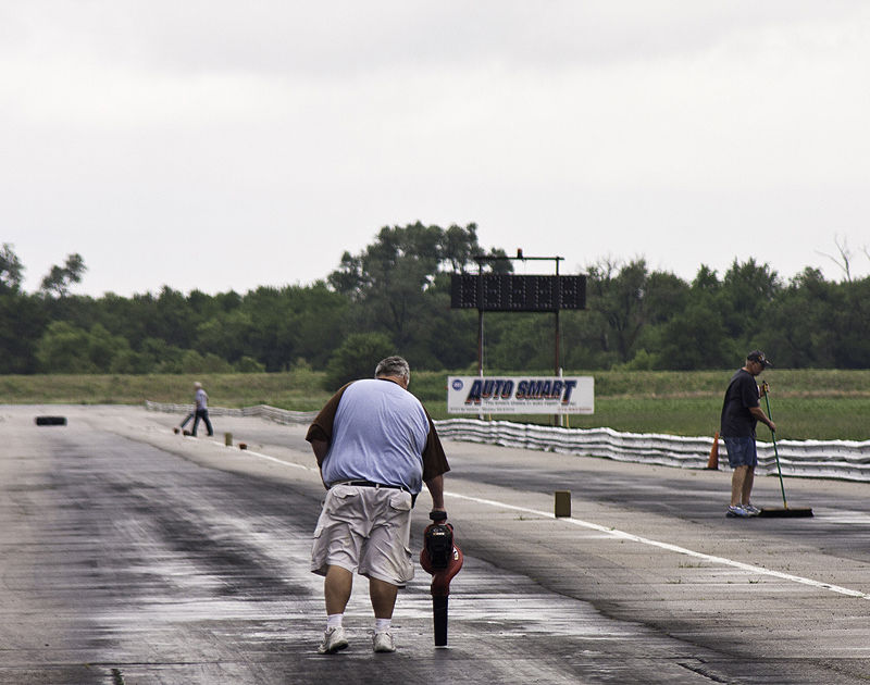 crew drying dragstrip with brooms and leafblower